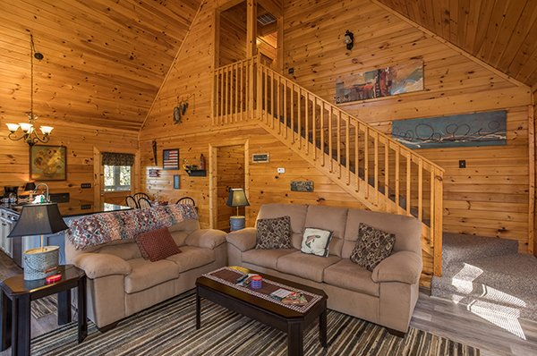 Seating in the living room with the open concept main floor behind at Lake Life, a 4 bedroom cabin rental located in Sevierville