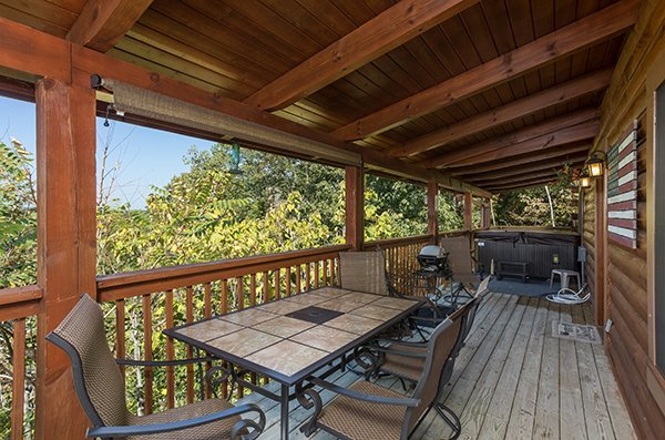 Covered deck dining space for four with a grill and hot tub in the background at Lake Life, a 4 bedroom cabin rental located in Sevierville
