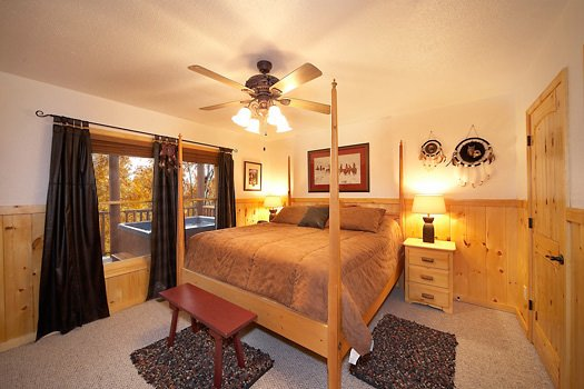 bedroom with king bed and attached jacuzzi bath at true grit a 5 bedroom cabin rental located in pigeon forge