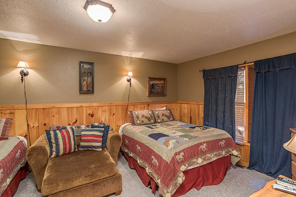 Bedroom with two queen beds and a large chair at True Grit, a 5 bedroom cabin rental located in Pigeon Forge