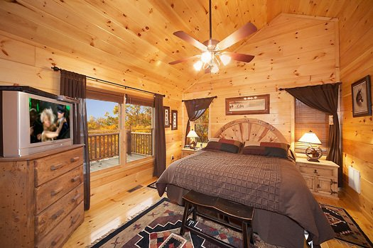 first floor bedroom with king bed and jacuzzi at true grit a 5 bedroom cabin rental located in pigeon forge