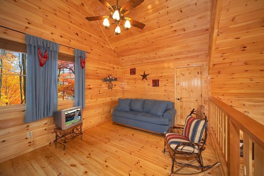Sofa and TV in the loft space at True Grit, a 5 bedroom cabin rental located in Pigeon Forge
