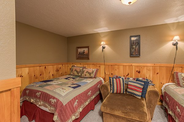 Two queen beds and a large chair in a bedroom at True Grit, a 5 bedroom cabin rental located in Pigeon Forge