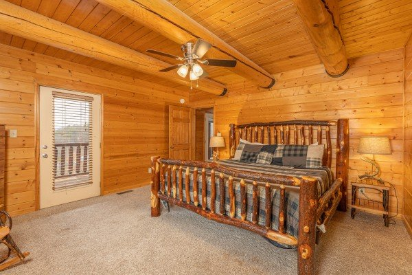 Bedroom with a king log bed, two night stands, and lamps at Smoky Mountain Escape, a 3 bedroom cabin rental located in Pigeon Forge