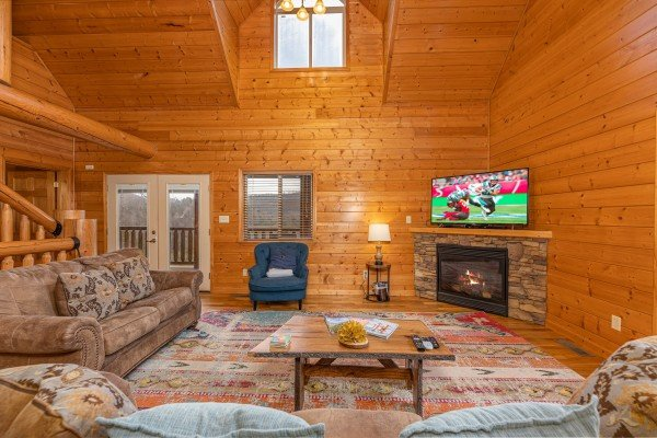 Seating, fireplace, and TV in a living room at Smoky Mountain Escape, a 3 bedroom cabin rental located in Pigeon Forge
