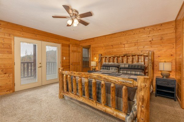 King log bed, two night stands, lamps, and deck access at Smoky Mountain Escape, a 3 bedroom cabin rental located in Pigeon Forge