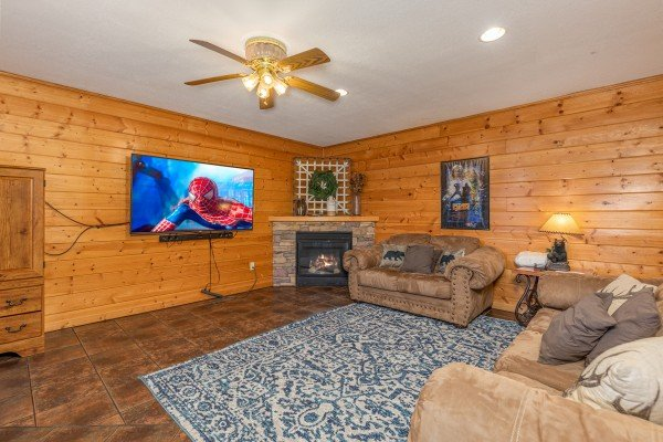 Fireplace and TV downstairs at Smoky Mountain Escape, a 3 bedroom cabin rental located in Pigeon Forge