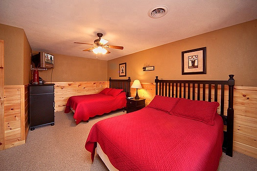 first floor bedroom with two full size beds at rainbow's end a 4 bedroom cabin rental located in pigeon forge