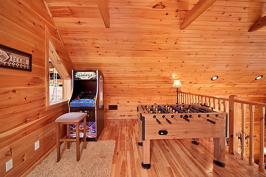 Lofted game room with foosball and arcade game at Rainbow's End, a 4 bedroom cabin rental located in Pigeon Forge
