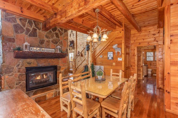 Dining room table with seating for six next to the fireplace at The Original American Dream, a 2 bedroom cabin rental located in Gatlinburg