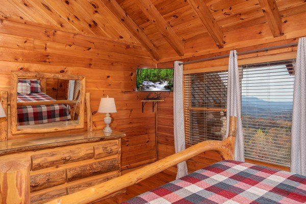 Bedroom with wall mounted television and mountain view at The Original American Dream, a 2 bedroom cabin rental located in Gatlinburg