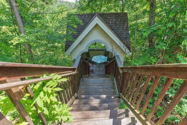 Looking down the stairs to the covered gazebo in the woods at Gatlinburg Movie Mansion, a 5-bedroom cabin rental located in Gatlinburg