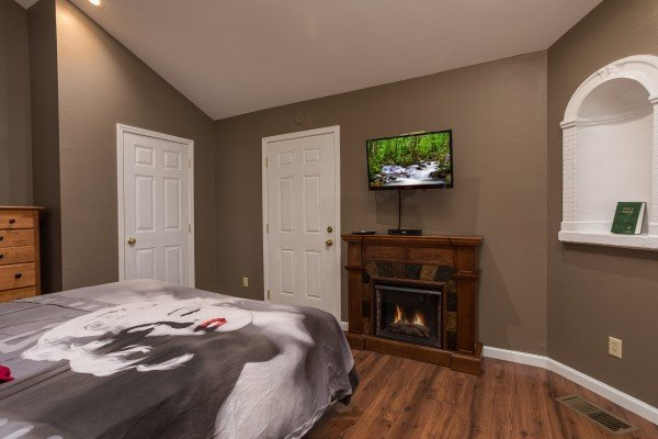 Bedroom with a king-sized bed, fireplace, and TV at Gatlinburg Movie Mansion, a 5-bedroom cabin rental located in Gatlinburg