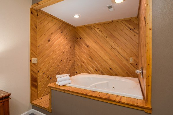 King bedroom with an in-room jacuzzi at Gatlinburg Movie Mansion, a 5-bedroom cabin rental located in Gatlinburg
