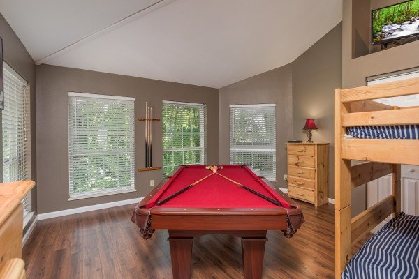 Pool table near a set of bunk beds at at Gatlinburg Movie Mansion, a 5-bedroom cabin rental located in Gatlinburg