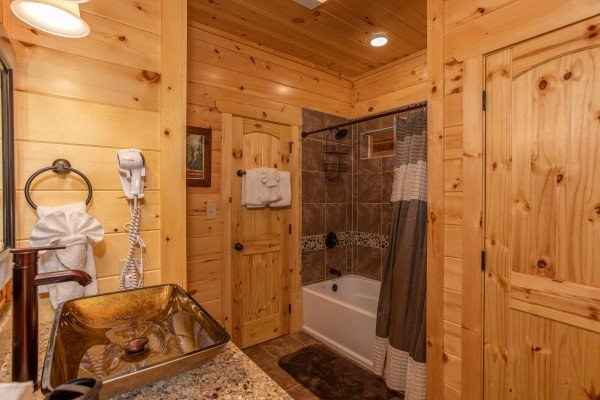 Tub and shower in a bathroom with a custom vanity at Panorama, a 2 bedroom cabin rental located in Pigeon Forge