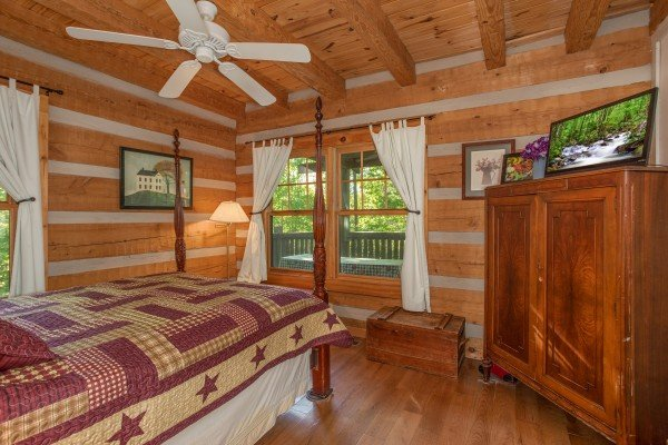 Bedroom with an armoire & TV at Trillium Lodge, a 4 bedroom cabin rental located in Gatlinburg