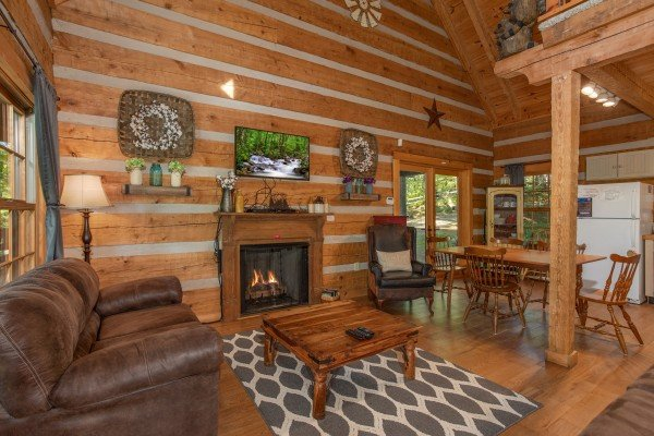 Living room with fireplace & dining room at Trillium Lodge, a 4 bedroom cabin rental located in Gatlinburg