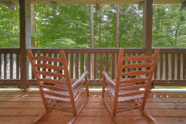 Rocking chairs on a covered deck at Trillium Lodge, a 4 bedroom cabin rental located in Gatlinburg