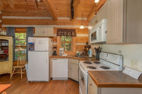 Looking into the kitchen with white appliances at Trillium Lodge, a 4 bedroom cabin rental located in Gatlinburg