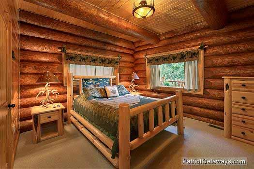 main level bedroom with queen bed at waters edge lodge a 4 bedroom cabin rental located in gatlinburg