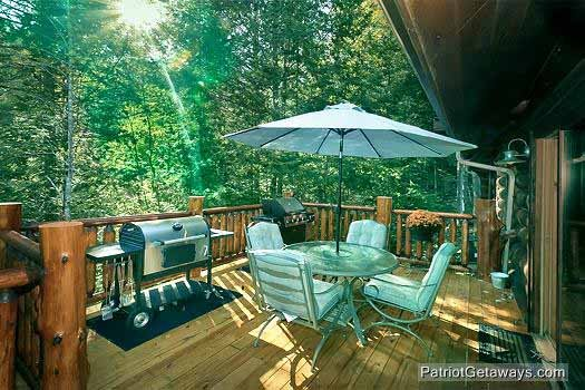 main level deck with grill and table at waters edge lodge a 4 bedroom cabin rental located in gatlinburg