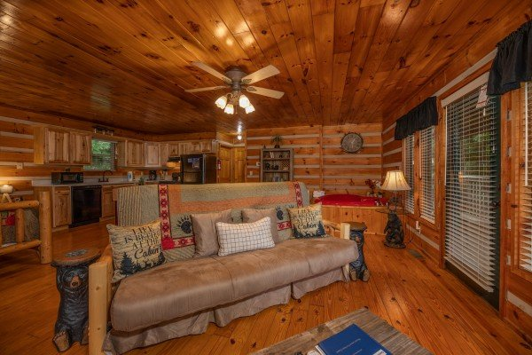 Futon in the living room at Honey Bear Hideaway, a 1 bedroom cabin rental located in Pigeon Forge
