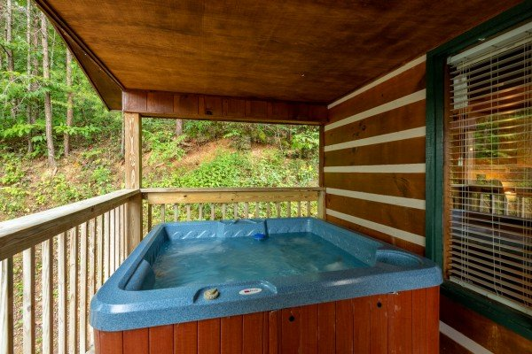 Hot tub on a covered deck at Honey Bear Hideaway, a 1 bedroom cabin rental located in Pigeon Forge