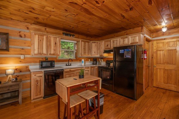 Kitchen with black appliances and dining table for two at Honey Bear Hideaway, a 1 bedroom cabin rental located in Pigeon Forge