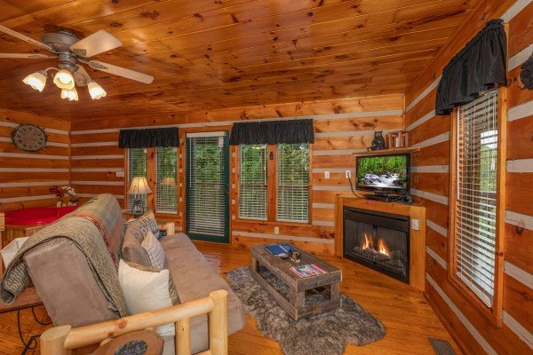 Living room with fireplace and TV at Honey Bear Hideaway, a 1 bedroom cabin rental located in Pigeon Forge