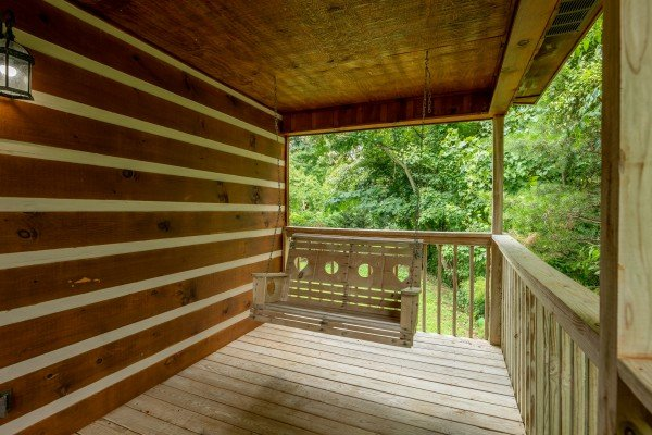 Porch swing on a covered deck at Honey Bear Hideaway, a 1 bedroom cabin rental located in Pigeon Forge
