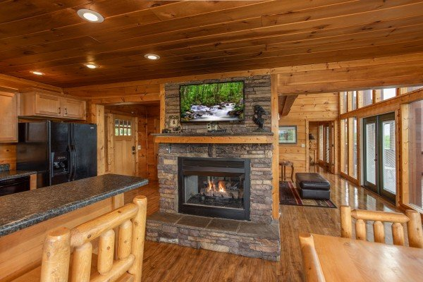 Fireplace and TV in the dining room at Mountain Bliss, a 2 bedroom cabin rental located in Pigeon Forge