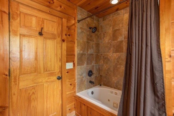 Bathroom with a jacuzzi and shower at Mountain Bliss, a 2 bedroom cabin rental located in Pigeon Forge