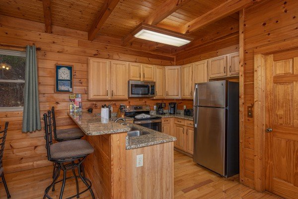 Breakfast bar and kitchen with stainless appliances at 1 Awesome View, a 3 bedroom cabin rental located in Pigeon Forge