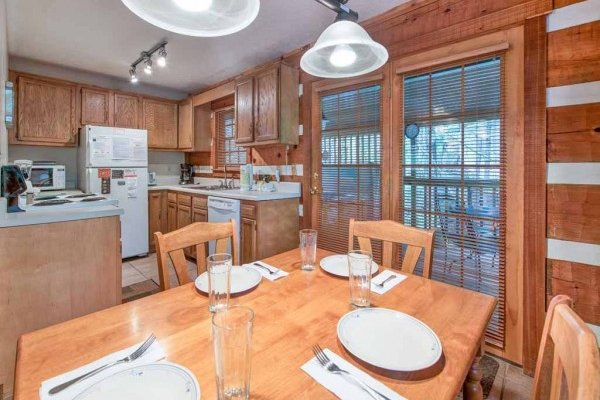Dining table for four and the kitchen at Wild at Heart, a 1 bedroom cabin rental located in Gatlinburg
