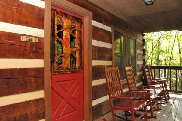 Front entry and rocking chairs on a covered porch at Wild at Heart, a 1 bedroom cabin rental located in Gatlinburg