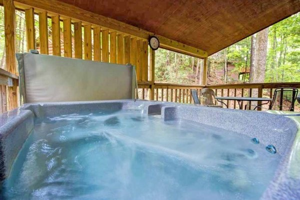 Hot tub on a covered deck at Wild at Heart, a 1 bedroom cabin rental located in Gatlinburg
