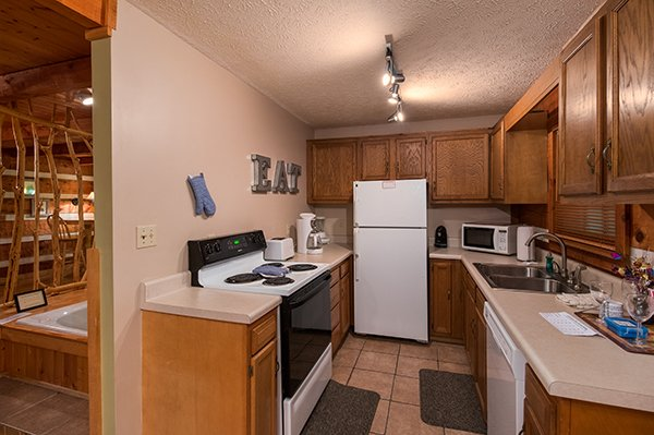 Kitchen with white appliances at Wild at Heart, a 1 bedroom cabin rental located in Gatlinburg