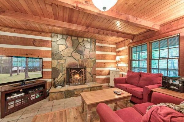 Living room with a fireplace and TV at Wild at Heart, a 1 bedroom cabin rental located in Gatlinburg