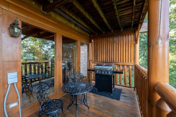 Grill and dining table for two on the deck at Rocky Top Retreat, a 2 bedroom cabin rental located in Pigeon Forge