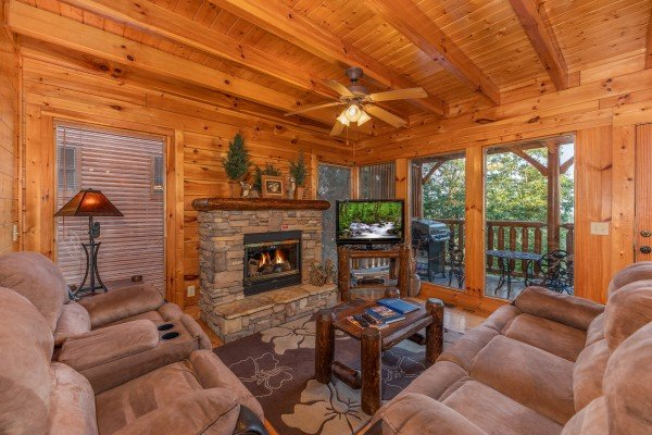 Living room with fireplace, TV, sofa, and loveseat at Rocky Top Retreat, a 2 bedroom cabin rental located in Pigeon Forge