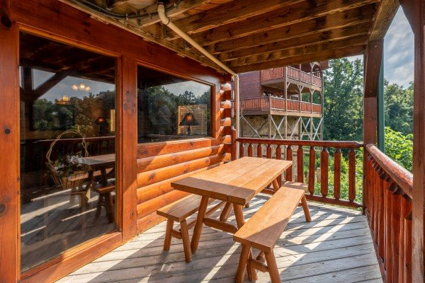 Picnic table on a covered deck at 1 Above the Smokies, a 2 bedroom cabin rental located in Pigeon Forge