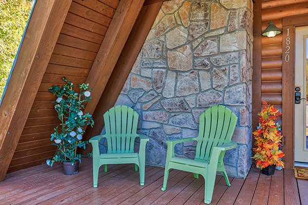 Two Adirondack chairs on the A-frame deck at Living on Love, a 2 bedroom cabin rental located in Pigeon Forge