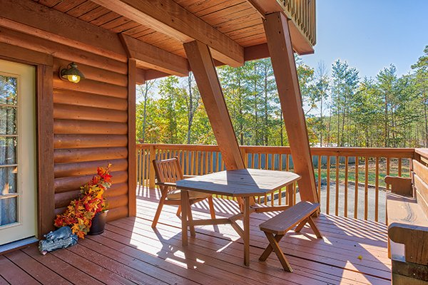 Deck with table and seating for two at Living on Love, a 2 bedroom cabin rental located in Pigeon Forge