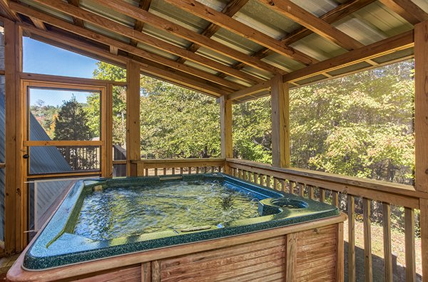 Hot tub on a screened in deck at Living on Love, a 2 bedroom cabin rental located in Pigeon Forge