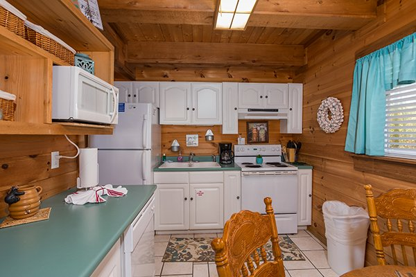Kitchen with white cabinets and appliances at Living on Love, a 2 bedroom cabin rental located in Pigeon Forge