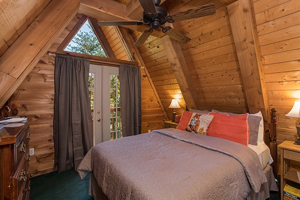 Bedroom with a queen bed and deck access at Living on Love, a 2 bedroom cabin rental located in Pigeon Forge