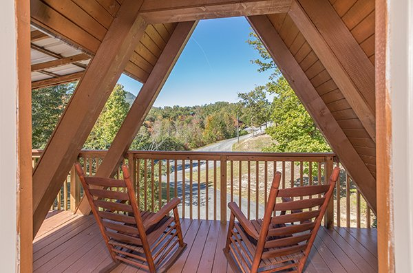 Two rocking chairs on the loft deck overlooking the drive at Living on Love, a 2 bedroom cabin rental located in Pigeon Forge