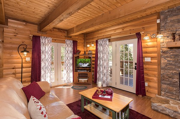 Living room with deck access at Living on Love, a 2 bedroom cabin rental located in Pigeon Forge