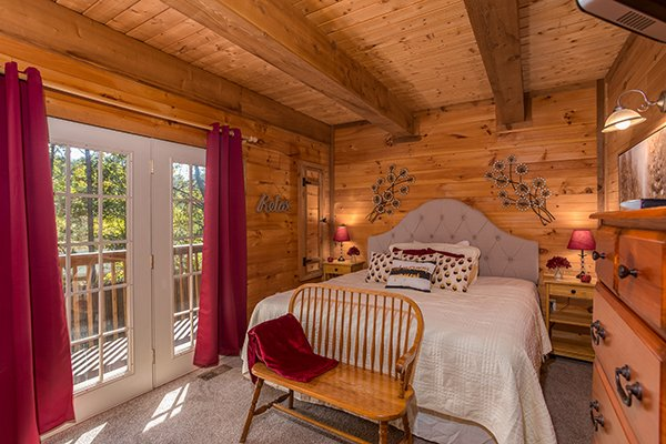 Bedroom with a king bed and a bench seat at Living on Love, a 2 bedroom cabin rental located in Pigeon Forge